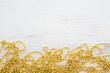 Gold Beads For Christmas Tree on white wood background. rustic style, top view.