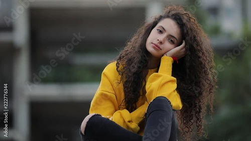 Teen girl in fashion yellow sweater sitting in urban city
