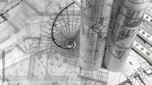 Blueprints - rolls of architectural drawings, yardstick - folding ruler and drawing of the golden section smoothly rotate on the surface of the architectural drawings