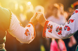 Girls in traditional Bulgarian ethnic costumes with red dresses and patterns on white shirts holding hands in the sunset. Concept of unity. Celebration - 222786775