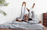 Happy couple lying on bed at home raising legs up - 222787129