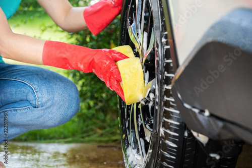 Poster woman holding sponge washing the wheels of car