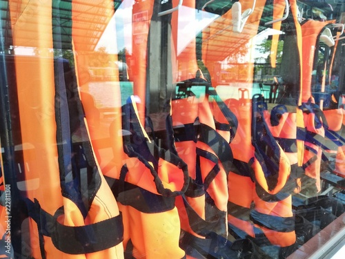 An orange life jacket hanging in a glass cabinet.