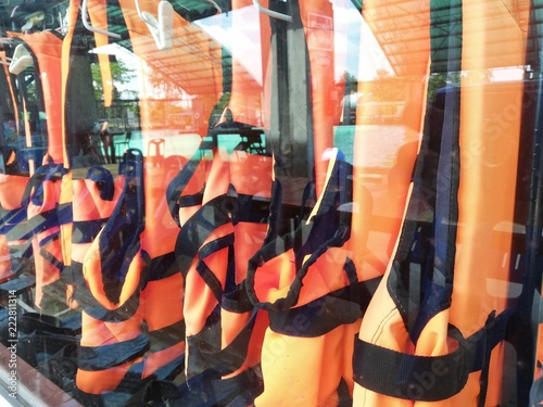 An orange life jacket hanging in a glass cabinet. - 222811314