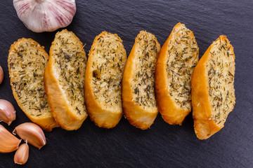 fragrant garlic bread on a dark stone plate