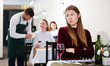 Elegant upset woman is expecting man for dinner in luxury restaurante