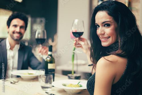 Leinwanddruck Bild Couple toasting wineglasses in a luxury restaurant, toned image