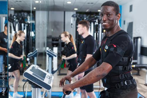 Leinwanddruck Bild Sporty man training EMS in gym