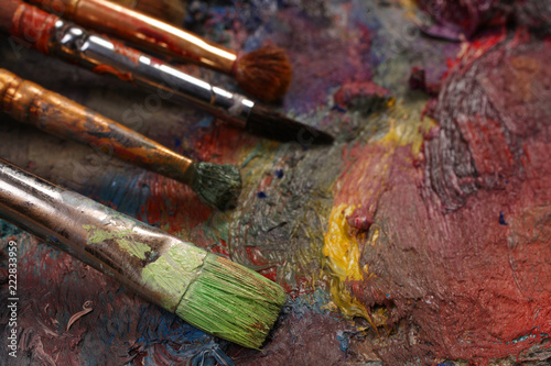 Paintbrushes closeup, artist palette and multicolor paint stains
