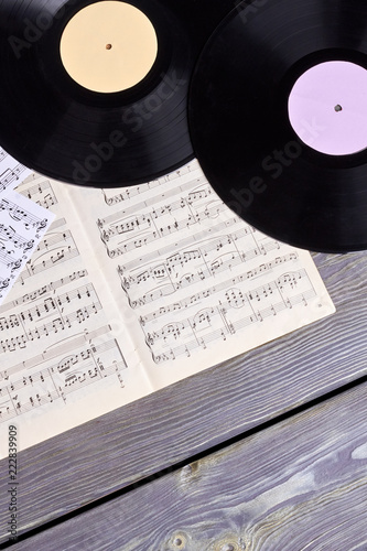 Vinyl records and musical notes sheets. Vinyl disc, musical notes pages on wooden background, top view. - 222839909