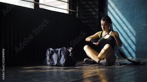 pasuje młoda kobieta z torbą siedzi na podłodze i zawijanie strony z bandażem. Żeński boksera atlety przygotowanie dla boksować szkolenie. wellness, walki, motywacja, koncepcja samoobrony