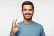 Young smiling man having happy look, gesturing, showing OK sign or showing okay gesture with his fingers