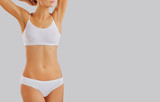 Slim body of a young woman in lingerie on a gray background. - 222854379