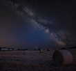 Vibrant Milky Way composite image over landscape of Lovely hay bales in English countryside