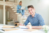 Laughing young designer sitting by table and reading papers while preparing for new project - 222857727