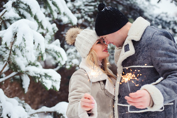 Outdoor portrait of happy romantic couple celebrating Christmas with burning fireworks in snowy forest. Runaway and travel on Holidays concept