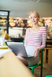 Young blonde manager in casualwear holding laptop on her knees while looking through online data in cafe - 222860399