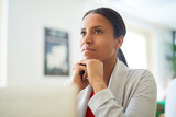 Young pensive mixed-race businesswoman keeping her hands under chin while thinking of something - 222861112