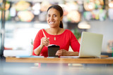 Positive young mixed-race woman eating chinese food from box while sitting by table with laptop in front - 222861758