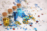 Bottles with colorful glitter on white - 222867173
