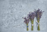 Three bouquet of lavender flowers on gray background. Copy space, top view. - 222870383