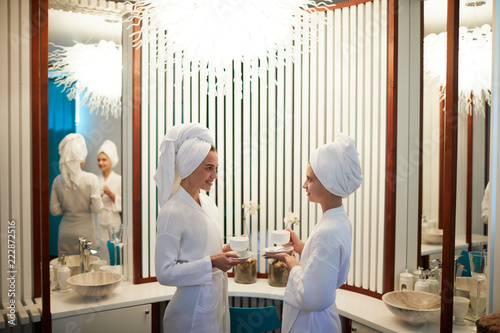 Two young women having tea in luxurious spa hotel after having bath or bodycare procedures