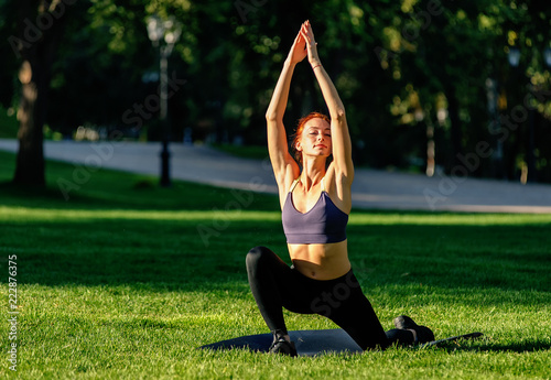 Poster Young woman doing yoga at the park