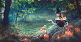Halloween Witch with a carved pumpkin and magic lights in a dark forest at night. Beautiful young woman in witches costume pointing hand - 222882138