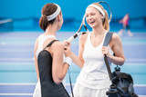 Waist up portrait of two beautiful young women laughing happily while chatting in indoor tennis court after practice - 222894921