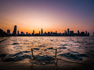 Chicago skyline picture during a beautiful sunset with purple and orange sky above the building silhouettes on the horizon with waves coming up over the concrete shoreline and emergency safety ladder.