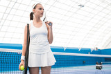 Portrait of motivated female tennis player posing with racket entering indoor tennis court, copy space - 222897354