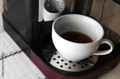 A white cup of coffee with prepaired drink still standing at the coffee machine platform. Breakfast and home equipment concept.