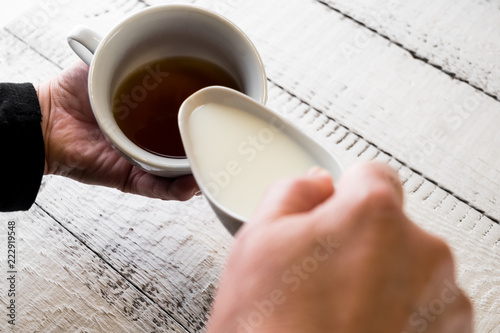 Woman pouring milk in to the cup of coffee to make a morning espresso. Breakfast and home equipment concept.