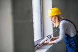 Young woman worker using silicone sealant gun on the construction site. - 222925580