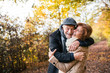 Leinwanddruck Bild - Senior couple standing in an autumn nature, hugging.