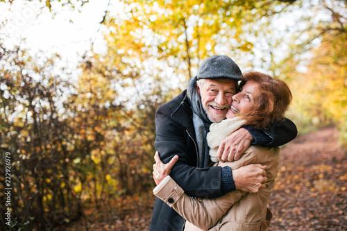 Leinwanddruck Bild Senior couple standing in an autumn nature, hugging.