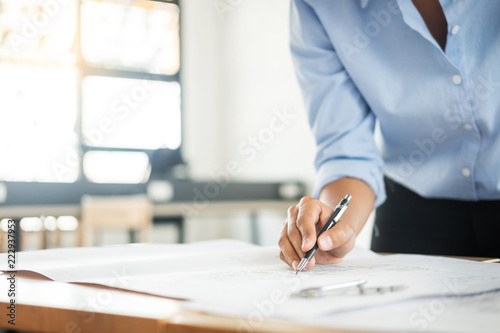 Fototapeta samoprzylepna Person's engineer Hand Drawing Plan On Blue Print with architect equipment, Architects working at the table.
