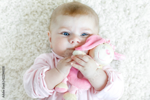 Cute baby girl playing with colorful pastel vintage rattle toy - 222946518