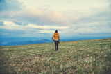 Woman standing on a empty mountain meadow.