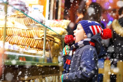Leinwandbild Motiv Happy child eating on apple covered with red sugar on Christmas market