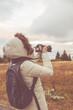 Woman using DSLR in mountain / suburb surroundings.