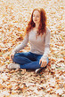 Leinwanddruck Bild - Young woman relaxing on autumn leaves in park