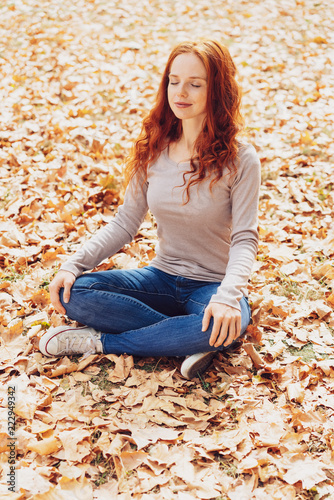 Young woman relaxing on autumn leaves in park - 222949342