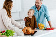 happy little child preparing thanksgiving dinner with parents