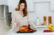 attractive happy woman cooking thanksgiving turkey at kitchen