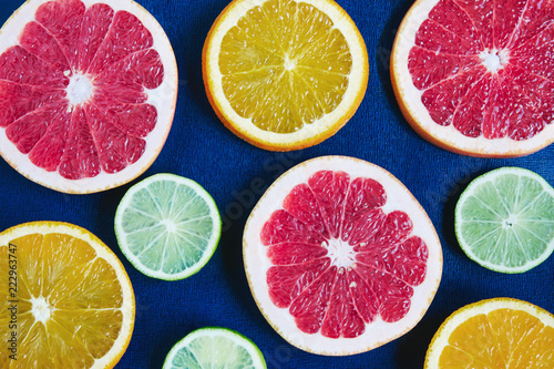 Blue background with citrus slices: orange, grapefruit, lemon, lime. Contrast of colors
