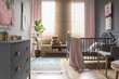 Leinwanddruck Bild - Teddy bear on wooden cupboard next to ficus in child's bedroom interior with cradle. Real photo