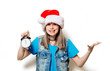 portrait of young teenage girl in Christmas hat with alarm clock on white background