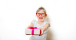 Portrait of an emotional toddler girl in white t-shirt and glasses with gift box on white background