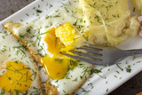 Fried eggs with melted Romanian cheese called cas - 222983547